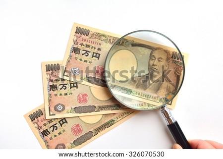 10 Thousand Japanese Yen bank notes under magnifying glass - stock photo