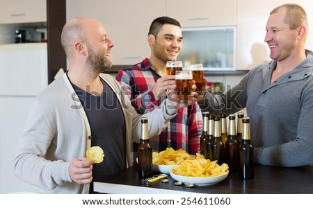 Three american guys drinking beer and laughing at house party - stock photo
