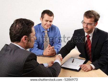 Three businessmen sitting at a table negotiating and signing a contract. handskake. - stock photo