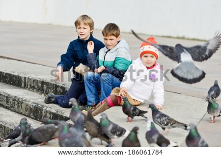 ��� three children feeding doves in the city