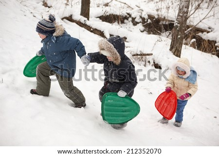 Three children with sledges/Three children are going on the hillside. Winter day - stock photo