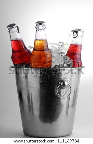 three different beer bottles in bucket of ice with condensation - stock photo