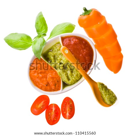 three different kinds of sauces in dishes for sauces, a branch of basil and ceramic spoon isolated on white background - stock photo
