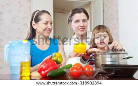 three generations of happy women cook vegetables in  kitchen at home - stock photo