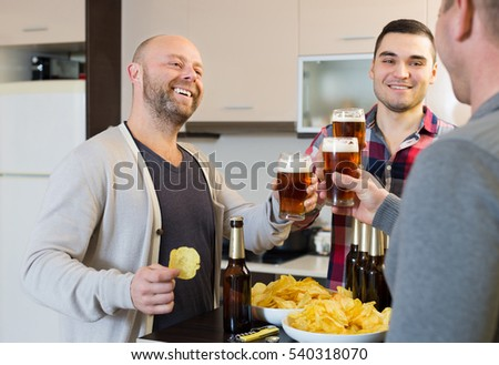 Three guys drinking beer and laughing at house