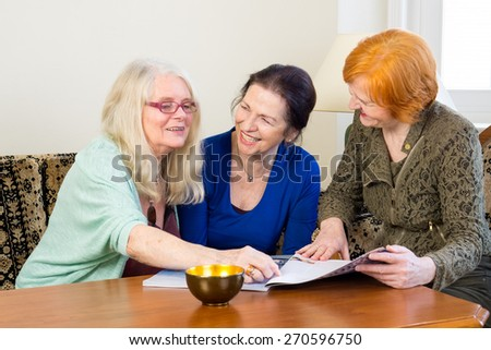 Three Happy Adult Women Friends Having Fun at the Living Room While Reading Magazine. - stock photo