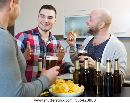 Three happy guys drinking beer and laughing at house party