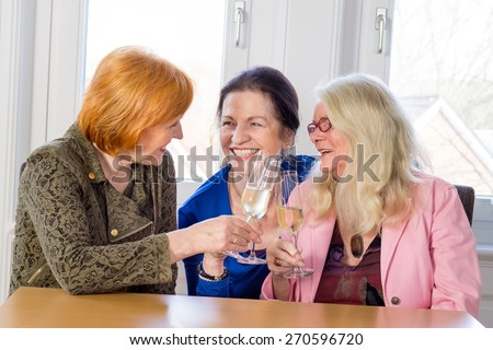 Three Happy Middle Age Mom Best Friends Tossing Glasses of White Wine and Smiling Each Other While Sitting at the Wooden Table Inside a Restaurant. - stock photo