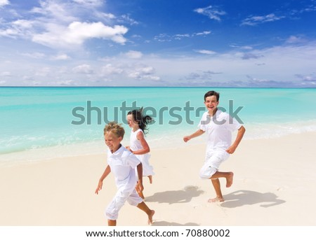 Three happy young children running and jumping on sandy tropical beach with sea and cloudscape in background. - stock photo