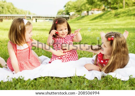 Three little sisters in red dresses having picnic outdoors. Three cute Caucasian little girls having a picnic in park playing together on sunny summer day.