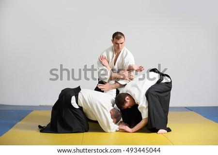 three men demonstrate  techniques of Aikido.