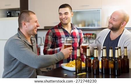 Three men drinking beer,eating chips and laughing at home - stock photo