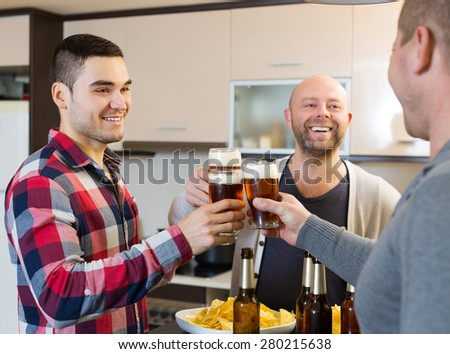 Three men drinking beer,eating chips and laughing at house party - stock photo