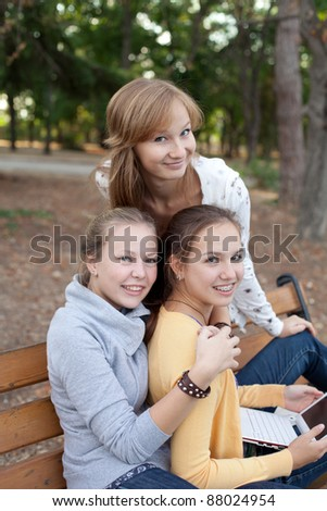 three pretty student girls sitting on the bench in the park - stock photo