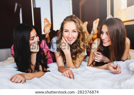 Three Pretty   young friends chatting on bed at home in the  cozy  bedroom.  - stock photo