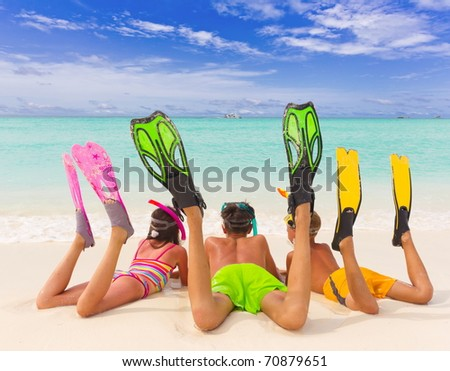 Three sibling children in bathing suits laying on the beach wearing flippers and snorkels by the water. - stock photo