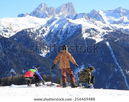 Three snowboarders mountains in the background - stock photo