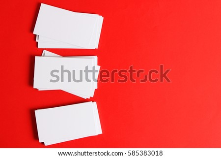 Three stacks ofwhite business cards on a red background with space for text.