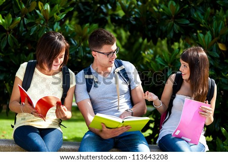 Three students on a bench in the park - stock photo