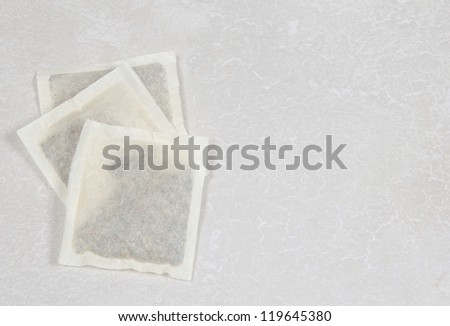 Three tea bags, green,herbal and black, on a white counter - stock photo