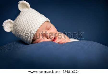 Three week old newborn baby boy wearing a brown crocheted bear hat and sleeping - stock photo