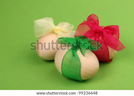 three wooden eggs with colorful ribbons on green background - stock photo