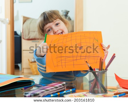 three year old child drawing on paper in home interior - stock photo