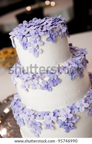 3 tiered wedding cake with purple flowers - stock photo