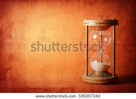 time concept with hourglass lying toned in warm orange and red colors, ancient sandglass - stock photo