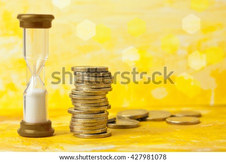'Time is money' concept: a photo of an hourglass with a pile of coins, against a blurred golden yellow background with copyspace - stock photo