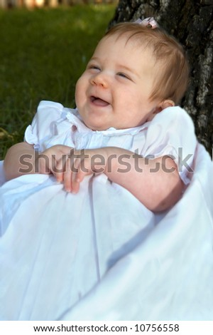 Tiny infant laughs at the camera.  She is propped against a tree trunk in yard.  She has a pink bow in her hair and a light pink dress on. - stock photo