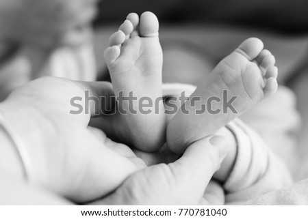 tiny newborn's foot in the mother hands in soft focus