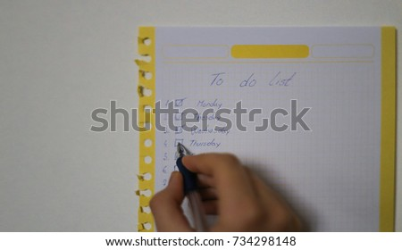 """To do list"" is written on notepad with pen on office table. Top View."