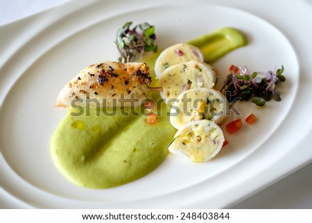 To Tani Ripieni - Squids, stuffed with their own tentacles and potatoes, served with green peas puree and fresh parsley pesto - stock photo