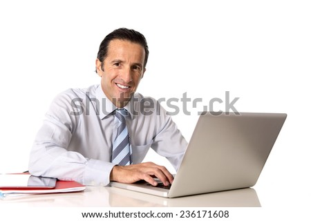 40 to 50 years old senior businessman working on computer laptop sitting at office desk looking confident, relaxed and successful isolated on white background - stock photo