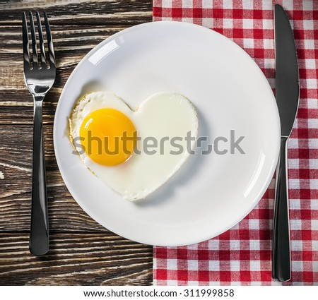 toast with scrambled eggs in the shape of a heart on a plate - stock photo