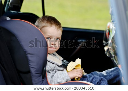 toddler boy sitting in the car seat and eating a banana - stock photo