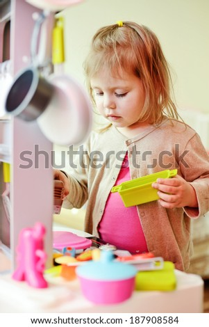 toddler girl playing with kitchen at home