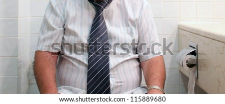 Toilet Problem.  A caucasian adult man wearing white shirt and tie  on toilet sea - stock photo