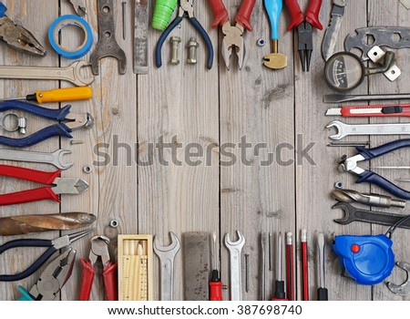 Tools on a wooden floor, top view. Empty space for Your text in the center.                             - stock photo