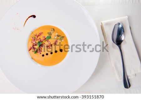 Top view Plate of Delicious Pumkin Cream soup with bacon in the round white plate  on the served restaurant table   - stock photo