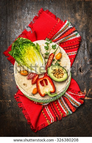 Tortillas and vegetables ingredients for burrito or tacos on dark wooden background, top view - stock photo