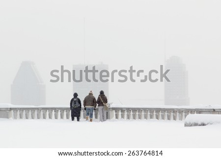 3 tourists looking at Montreal downtown under a snowstorm during winter - stock photo