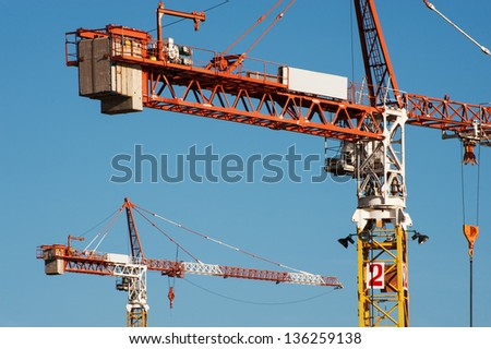 2 tower cranes on a blue sky background - stock photo