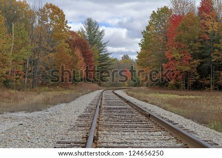 """Tracking Autumn"" -- Train tracks curve into the woods near Cadillac, Michigan - stock photo"