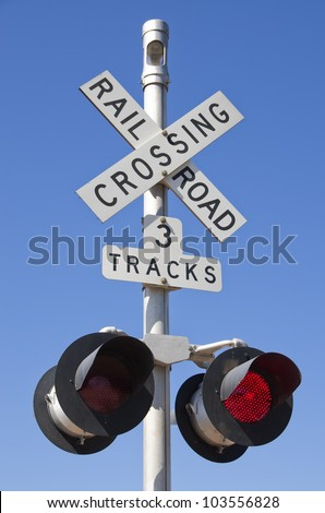 3 tracks railroad crossing sign with blinking red lights - stock photo