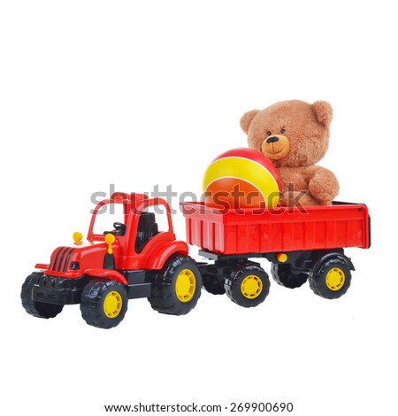 tractor carries a Teddy bear and a ball isolated on a white background - stock photo