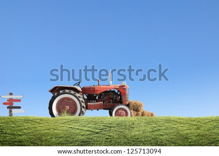 tractor collecting haystack in the field at nice blue - stock photo