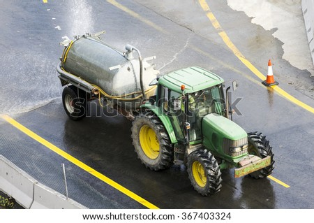 tractor machine  vehicle in  cleaning the  highway  with high pressure water - stock photo