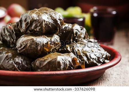 Traditional Greek dolma with meat in grape leaves, yogurt sauce, grapes and red wine on a clay dish, selective focus - stock photo
